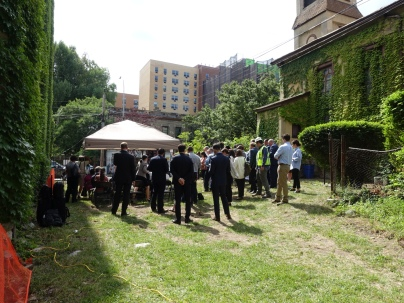 People gathered for remarks and refreshments on a lot behind the project site.